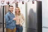 usmívající se přítelkyně a přítel ukazuje prstem na ledničku v obchodě se spotřebiči