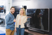 Photo smiling boyfriend showing like and girlfriend pointing with hand at tv in home appliance store