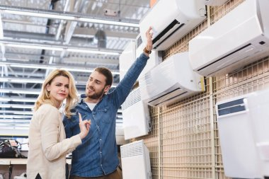 boyfriend pointing with hand at air conditioner and girlfriend showing no gesture in home appliance store