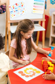 Gyerekek játszanak homokóra és oktatási játék íróasztal Montessori iskolában
