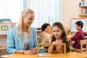 Mosolygó gyermek néz kamera közben oktatási játék tanár Montessori iskolában