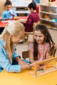 Szelektív fókusz a gyerek és a tanár mosolyog egymásra, miközben játszik a gyerekekkel a háttérben a montessori iskolában
