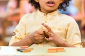 Oříznutý pohled na dítě hraje dřevěnou hru u stolu v Montessori škole
