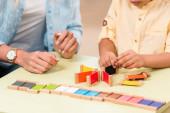 Vágott nézet a gyerek és a tanár játszik oktatási játék az asztalnál során lecke Montessori osztály