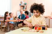 Szelektív fókusz afro-amerikai gyerek játszik oktatási játék tanár és a gyermekek a háttérben Montessori iskolában