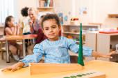 Szelektív fókusz a gyermek játék és tanár gyerekekkel a háttérben Montessori iskolában