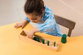 Pohled shora na africké americké dítě hrající dřevěnou hru u stolu ve škole Montessori