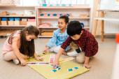 Children playing educational game on floor in montessori school