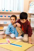 Fotografie Děti si hrají s barevnou hrou na koberci ve třídě montessori