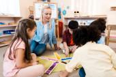 Gyerekek játszanak oktatási játék tanár a padlón Montessori osztály