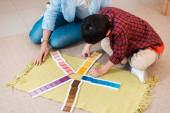 Vysoký úhel pohledu na učitele a dítě hrát barevnou hru na podlaze ve škole montessori