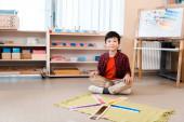 Usmívající se asijské dítě při pohledu na kameru podle vzdělávací hry na podlaze v Montessori škole