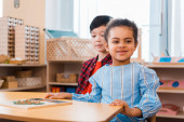 Děti s dřevěnou hrou na stole ve škole Montessori