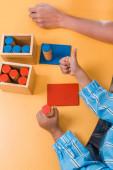 Vysoký úhel pohledu na dítě ukazující palec nahoru podle dřevěné hry a učitel ve škole montessori, oříznutý pohled