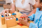 Selektivní zaměření dětí a učitelů hrát vzdělávací hru na stole v Montessori škole