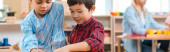Panoráma felvétel a gyerekek tanítás közben Montessori osztály tanár a háttérben
