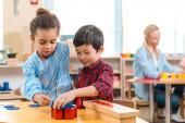 Szelektív fókusz a gyerekek összecsukható oktatási játék tanár a háttérben Montessori osztály