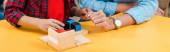 Oříznutý pohled na učitele a dítě hrající stavební kameny na stole ve třídě montessori, panoramatický záběr