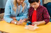 Asijské dítě hrát stavební kameny podle učitel v montessori třídě