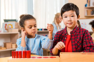 Selective focus of children with board game at desk with teacher and kids at background in montessori class stock vector