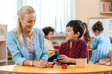 Selective focus of smiling teacher and kid playing building blocks with children at background in montessori school stock vector