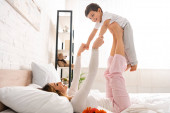 šťastná žena baví s rozkošným synem v posteli v den matek