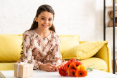cheerful child in elegant dress looking at camera while sitting near table with flowers and gift box