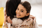 Photo adorable, happy child smiling at camera while embracing mom on mothers day