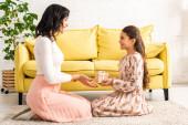 boční pohled na elegantní dcera představující matky den dárek pro maminku, zatímco sedí na podlaze spolu
