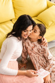 Photo happy woman holding mothers day card while adorable daughter kissing her