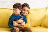 Fotografie šťastný dítě objímání rozkošný bratr zatímco sedí na žluté pohovce doma