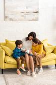 šťastná matka a děti sedí na žluté pohovce s bílým králíkem