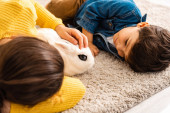 cute brother and sister lying on floor near white funny rabbit