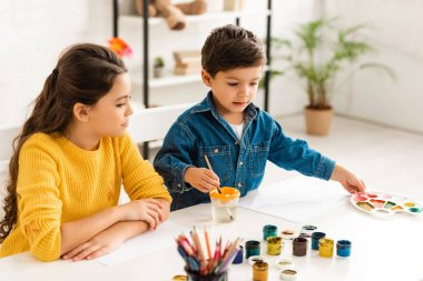 cute boy dipping paintbrush in water and touching palette while sitting at table near sister