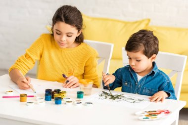 Attentive, adorable children sitting at table and drawing with paints together stock vector