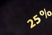 Photo top view of golden 25 percent signs on black background