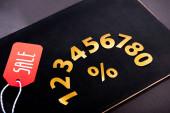 zlatá čísla se znaménkem procent a červenou cenovkou s nápisem prodeje na černém pozadí