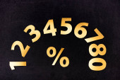 horní pohled na zlatá čísla a procenta znamení na černém pozadí