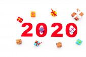 Draufsicht auf rote 2020 Zahl und Geschenke isoliert auf weiß
