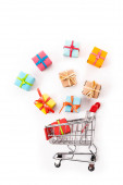 top view of decorative small shopping cart near gift boxes isolated on white