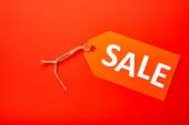 Draufsicht auf Preisschild mit Verkaufsbuchstaben isoliert auf Rot