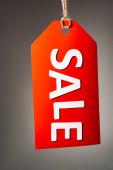 červená cenovka s prodejním nápisem na černém pozadí