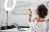 side view of boldog afro-amerikai befolyásoló fogszabályzóban tartja hitelkártya közelében laptop