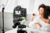 selektiver Fokus der Digitalkamera mit afrikanisch-amerikanischem Influencer, der Behälter mit Gesichtscreme auf dem Display hält