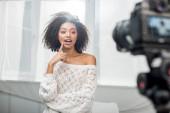 Selektiver Fokus der überraschten afrikanisch-amerikanischen Influencerin in Zahnspange, die das Gesicht in der Nähe der Digitalkamera berührt