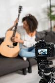 selektivní zaměření digitálního fotoaparátu s mladou africkou americkou dívkou hrající na akustickou kytaru