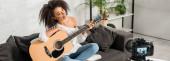 panoramatický záběr veselé africké americké dívky v rovnátka drží akustickou kytaru a při pohledu na digitální fotoaparát