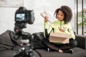Selektiver Fokus sportlicher afrikanisch-amerikanischer Influencer in Hosenträgern mit neuem Sneaker in der Nähe von Box und Digitalkamera