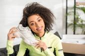 Fotografie fröhliche afrikanisch-amerikanische Influencerin in Sportbekleidung mit neuem Turnschuh