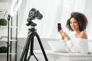 Selective focus of of digital camera near attractive african american video blogger in braces pointing with finger at smartphone with blank screen stock vector